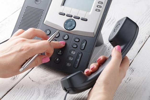 電話のキーを押す1つの人間の手