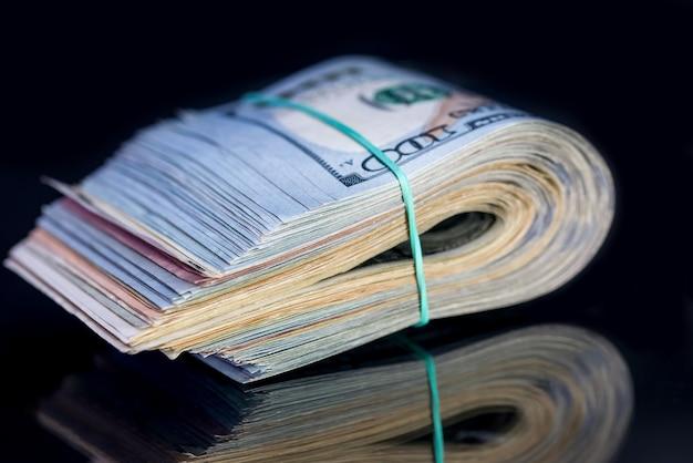 Банкноты ста американских долларов с полосой, изолированные на черном фоне.
