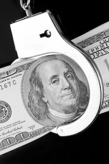 Банкнота в сто долларов в наручниках