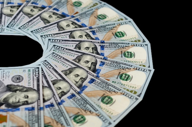 One hundred dollar bills are fanned out on a black background. top side view.