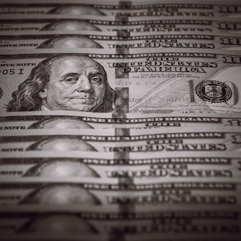 One hundred dollar bills are in a row, one stands out, selective focus. style black and white.