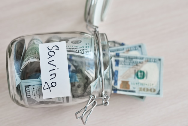 One hundred dollar bills in glass jar with inscription saving on table. saving money and home finance concept