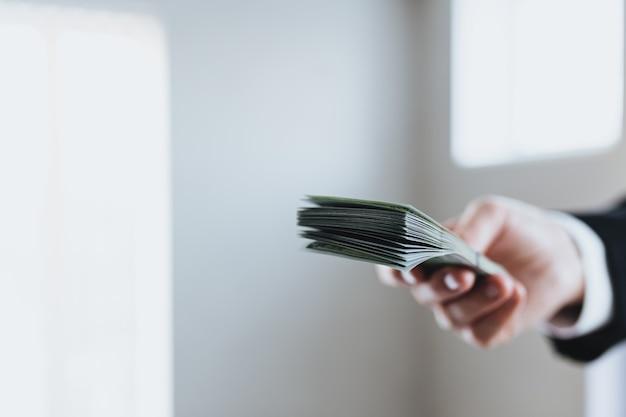 양복과 흰색 셔츠를 입은 남자의 손에 100 달러 지폐 돈 묶음