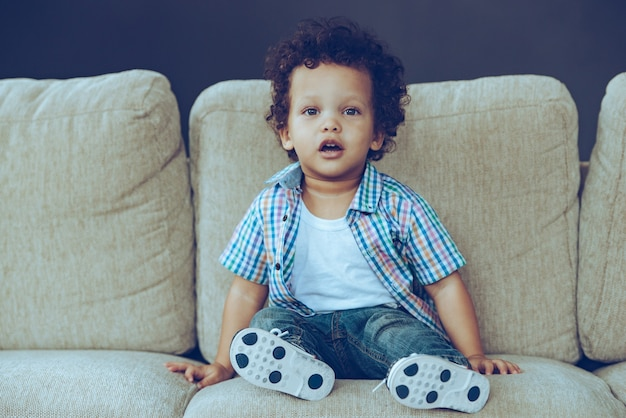 One hundred percent cute! little african baby boy looking at camera while sitting on the couch at home