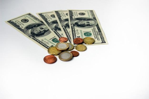 Сто долларовая банкнота или банкноты с монетами центов и евро на белом фоне