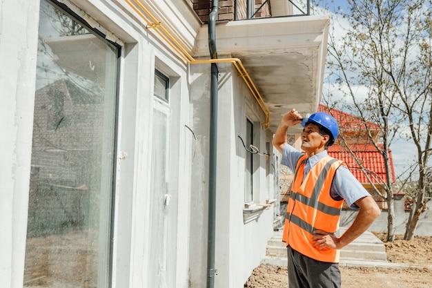 建設現場での作業を検査するヘルメットとベストの労働者の1人のインドのビルダー建設労働者が建設を管理している