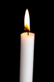 One isolated white candle burning on a black background. white candle flame in the dark