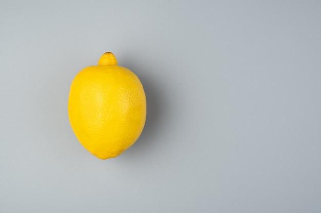 灰色の背景に1つのジューシーな熟したレモン。コピーするスペースのある上面図。