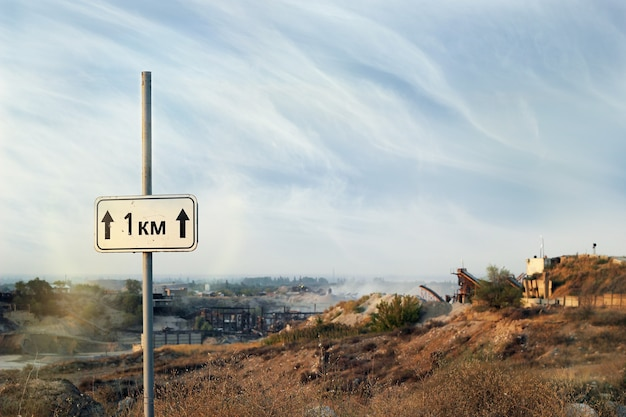 One kilometer sign on a country deserted road to industrial zone