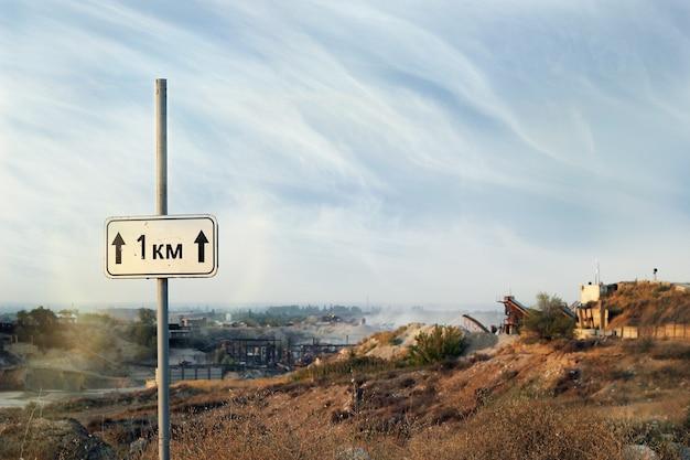 工業地帯への田舎の人けのない道の1キロの標識