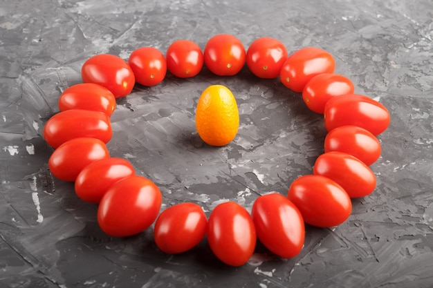 One kumquat in a circle of cherry tomatoes on a black concrete background