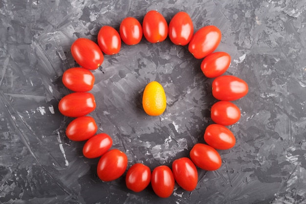 One kumquat in a circle of cherry tomatoes on black