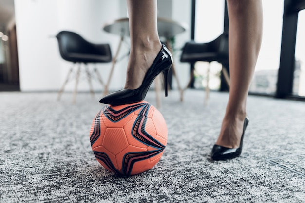One leg stands on an orange soccer ball.