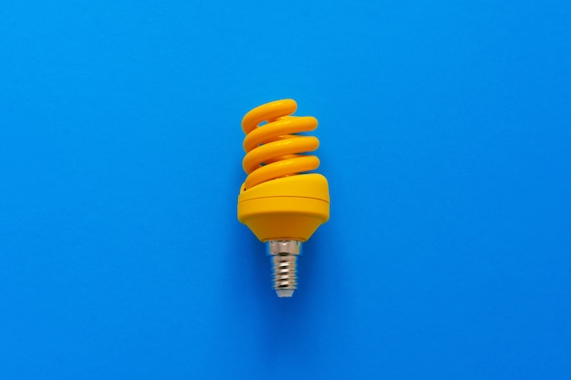 One light bulb on a blue paper background
