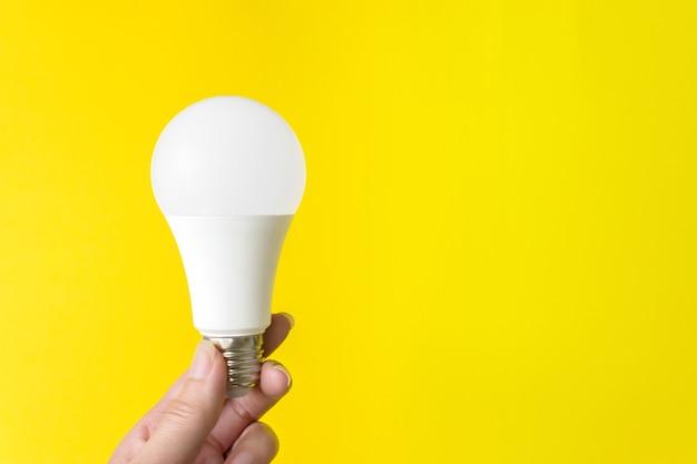 Одна лампочка в руке на желтом фоне. новая энергетическая технология. скопируйте пространство.