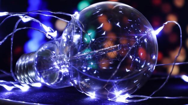 1つの電球は、背景にライトが付いた黒い背景にあります。創造的なアイデアのコンセプト。ちらつき電球とカラフルな背景。休日のコンセプト。元日とクリスマス。