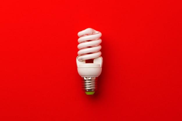 Одна лампочка на красной поверхности вид сверху