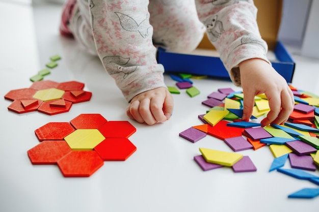 One little kids play with puzzle or tangram, education