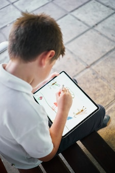 Один маленький испанский школьник, рисунок на планшете, сидя на скамейке в парке
