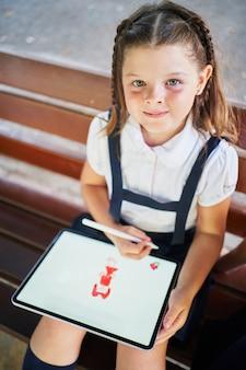 Одна маленькая испанская школьница рисует на планшете в парке, улыбаясь в камеру