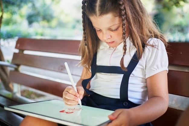 Одна маленькая испанская школьница рисует на планшете в парке