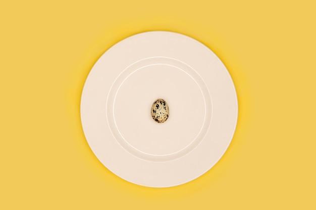 Одно перепелиное яйцо на белой тарелке. минимальный минимализм. диетическое питание, снижение калорийности, диета для похудения, сжигание жира. вид сверху. белок кето, здоровое питание, питание