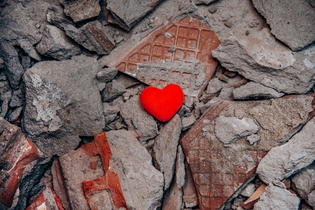 One lonely heart against background of broken concrete fragments. unhappy love relationships. infidelity and betrayal. difficult period in family life. quarrel. endured scandal. love against all odds.