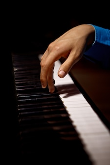 Одна мужская рука на пианино.