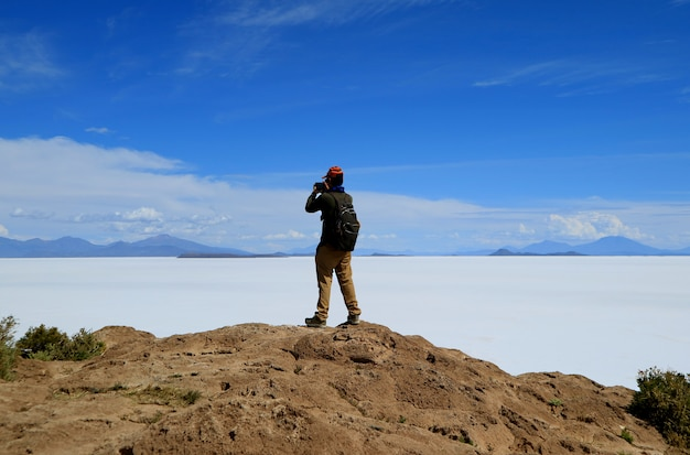 One male tourist taking photos of the imense uyuni salt flats from isla incahuasi, potosi, bolivia