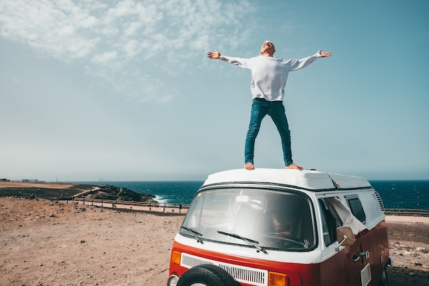 One man alone and isolated standing with opened arms on a minivan or camper having fun and smiling