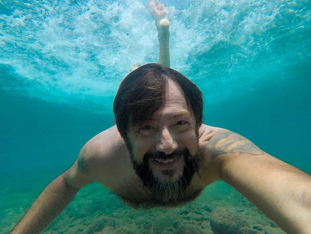Один мужчина плавает в одиночестве под водой и держит камеру, глядя на нее, улыбаясь и развлекаясь в море - взрослый плавает в воде, наслаждаясь отпуском