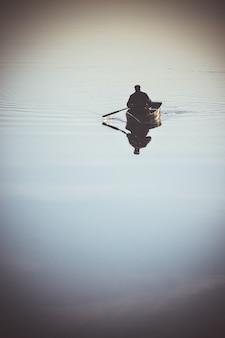 작은 보트에 한 남자가 노를 노를 호수 강에 범선. 물의 매끄러운 거울 표면이 있는 강. 날씨 조용함, 고요함, 바람 없음