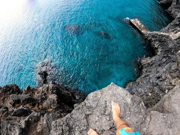 Один мужчина в видео от первого лица или от первого лица прыгает со скалы в воду моря или океана на пляже