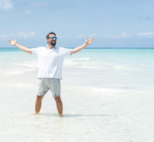 一人の男が美しい熱帯のビーチを楽しんでいます Premium写真