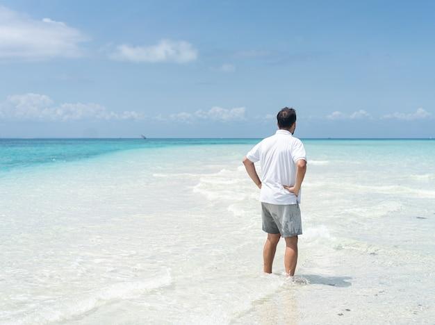 한 남자가 아름다운 열대 해변을 즐기고 있습니다