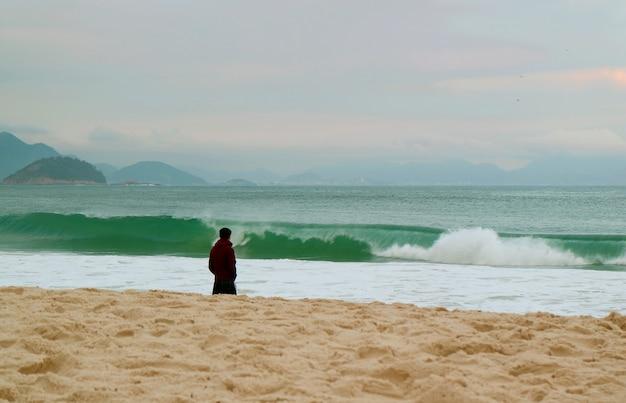 Один мужчина на песчаном пляже, глядя на волнистое море