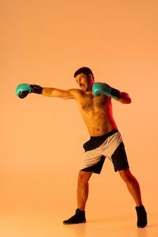 One man professional boxer in sportwear boxing on studio wall in gradient neon light
