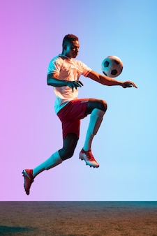 One man professional soccer football player training isolated on gradient wall