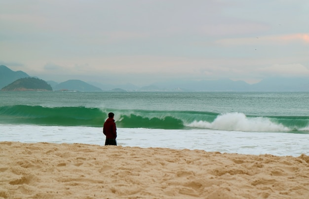 One man on the sandy beach looking at the wavy sea