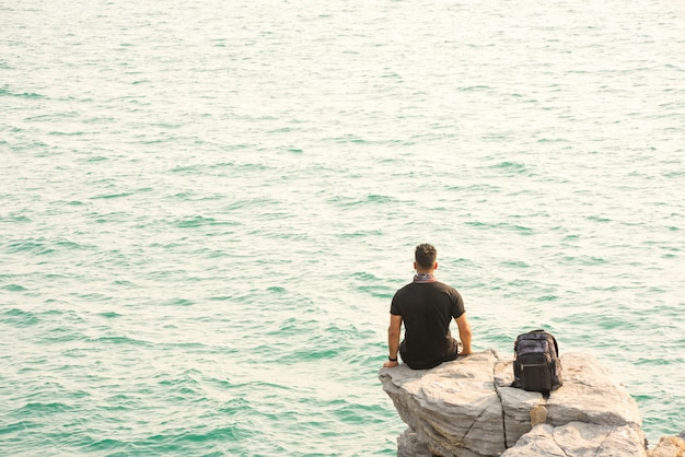 One man sit in back on rock by the sea with backpack.