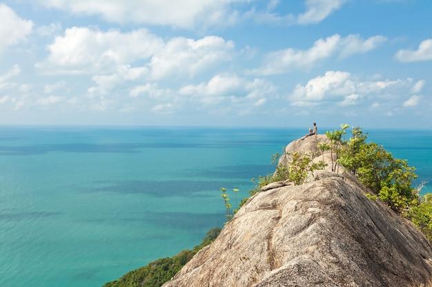 一人の男が見事な海の景色を望む丘の上に座っている