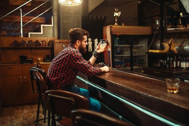 Один мужчина сидит за барной стойкой и пьет алкогольный напиток. мужчина в пабе