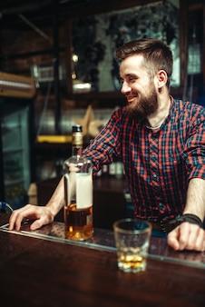 Один мужчина стоит у стойки бара, пьянство