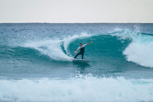 Один мужчина тренируется и занимается серфингом в отпуске летом или зимой в гидрокостюме - красивая и большая волна на канарских островах