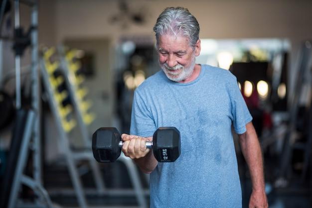 健康とフィットネスのために運動をしているジムで体重を保持している1人の成熟した男性-ダンベルを保持している活動をしているジムの先輩