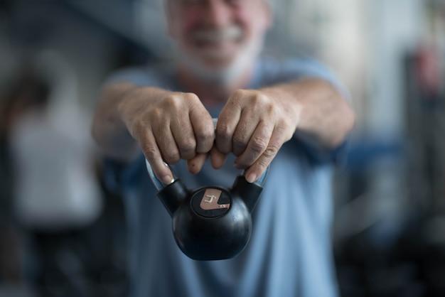 健康とフィットネスのために運動をしているジムで体重を保持している1人の成熟した男性-活動をしているジムの先輩