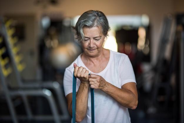 健康でフィットネスのシニアになるためにジムで1人の成熟した女性のdoig運動-毎日のライフスタイルとコンセプトのトレーニング