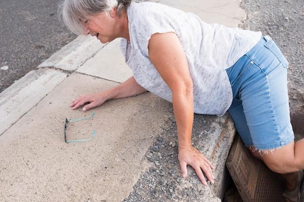 一人の成熟した女性が助けを必要としている通りの穴に落ちる-穴の中に足を入れて歩く-prolematicsenior