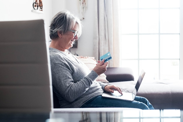 One mature woman on the sofa using her laptop and her credit card to buy something  - shopping online concept and shopaholic - senior at home doing gifts and presents with the sales