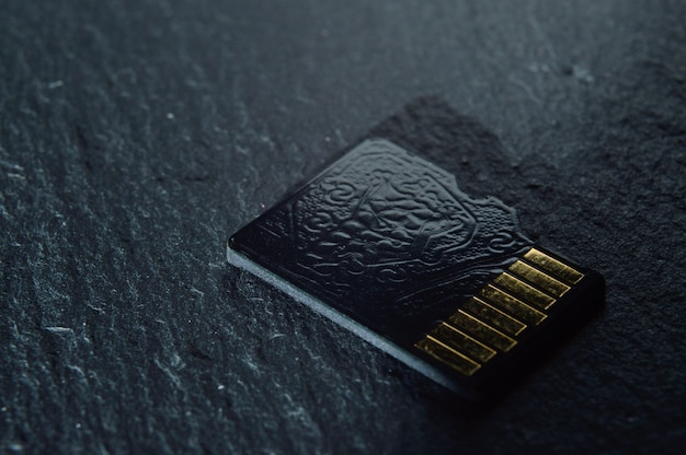 마이크로 sd 카드 1 개가 놓여 있으며 상단에 금색 접점이 있습니다. 확대.
